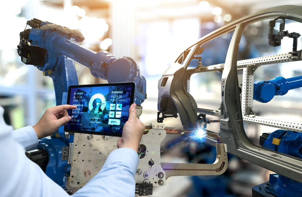 Engineer examines automotive parts in a factory while holding a tablet